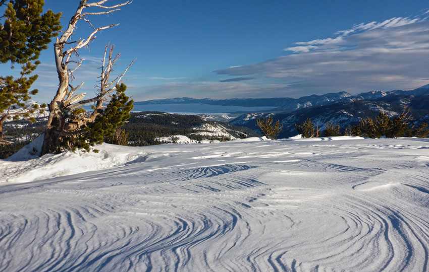 Wind-scoured snow atop a mountain with Lake Tahoe in the background