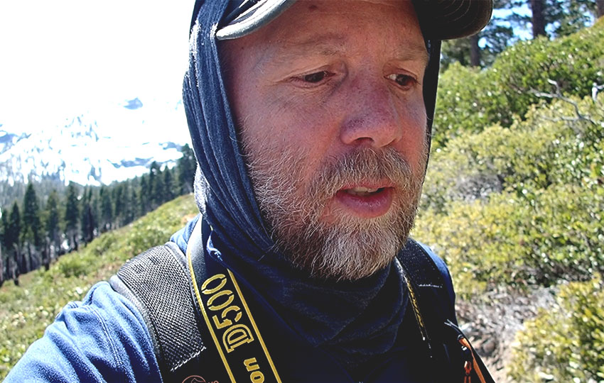 Man hiking in mountains with camera around his neck