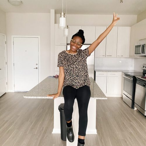A woman sitting on her kitchen counter celebrating her new apartment.