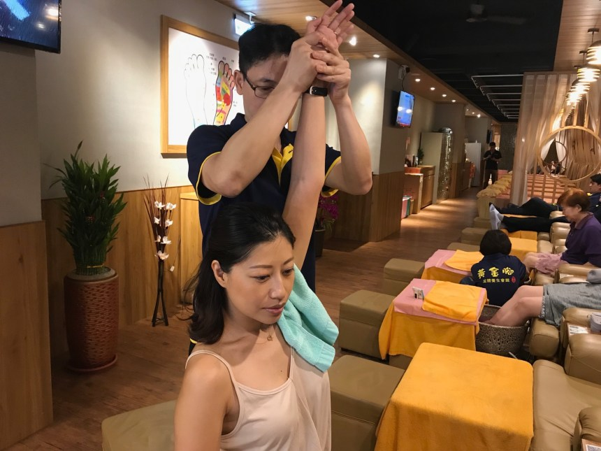 The massage therapist in Taipei stretching guest's arms to relax her shoulder and back.