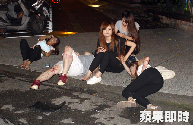 Injured driver and passengers wait for an ambulance after a car crash
