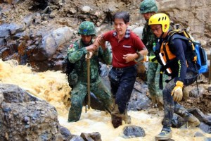 Soldiers help a man cross over debris and a torrent of flood water near Wulai Township