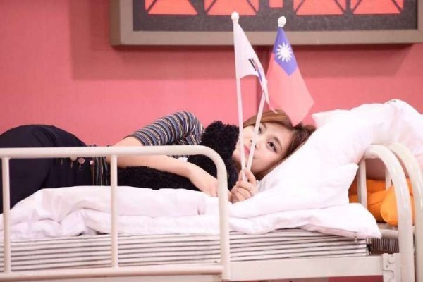 Zhou Ziyu poses with the Korean and Republic of China (Taiwan) flags on a Korean variety show