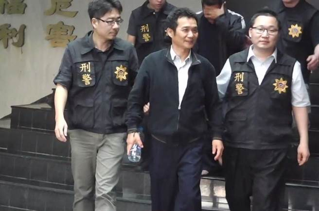 Mayor Wan Kun-hong being brought in to be arraigned on charges of paying to murder his rival in love