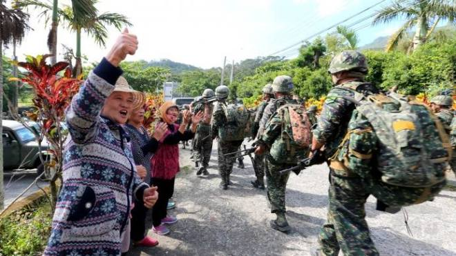 rural villagers urge troops on as they embark on a 250 kilometer loaded march.