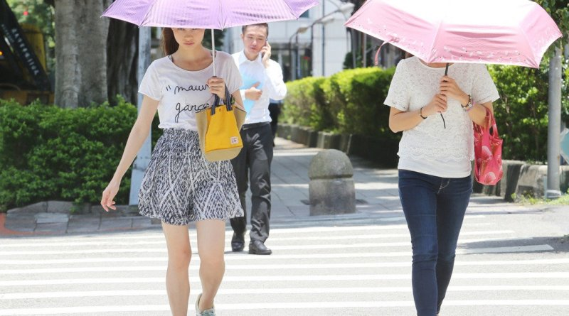 Pedestrians use umbrellas as sun-protection in Taipei City