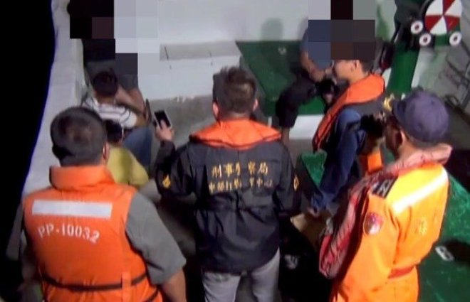 coastguard officers question suspected illegal immigrants on a Chinese fishing vessel off the coast of southern Taiwan April 9, 2017