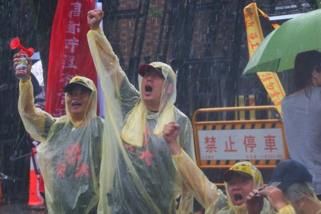 protesters defy the rain during a downpour April 19, 2017