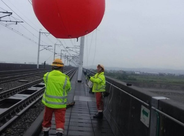 workers remove balloon from power lines