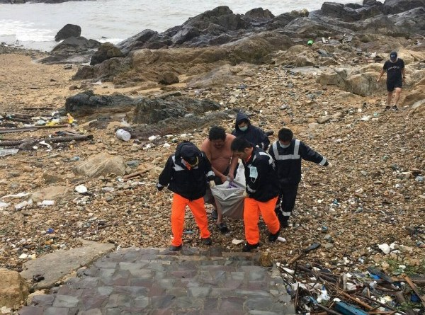 coast guard officers recover human remains on the shore