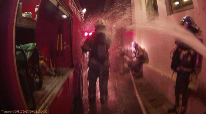 A firefighter hoses down a colleague covered in acid