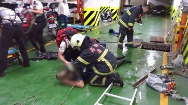 firefighters and paramedics attempt to rescue workers from sewage tank