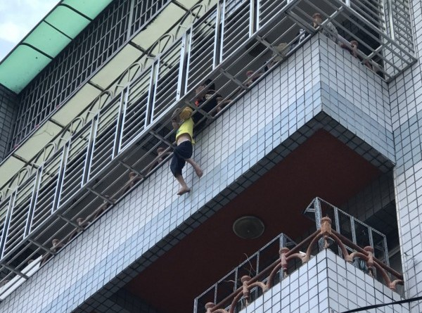 boy dangling from balcony security grill