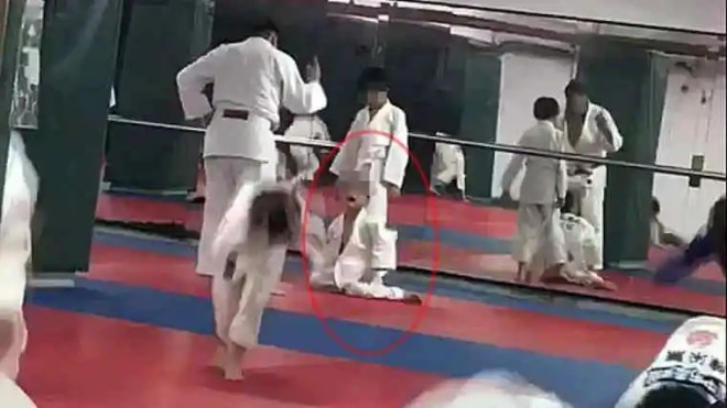 A judo coach orders a boy to stand up after the boy cries and complains that his legs hurt.