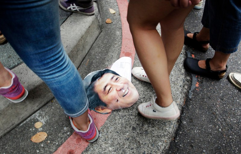 Activists step over a picture of Shinzo Abe during a protest in front of the Japan Interchange Association in Taipei