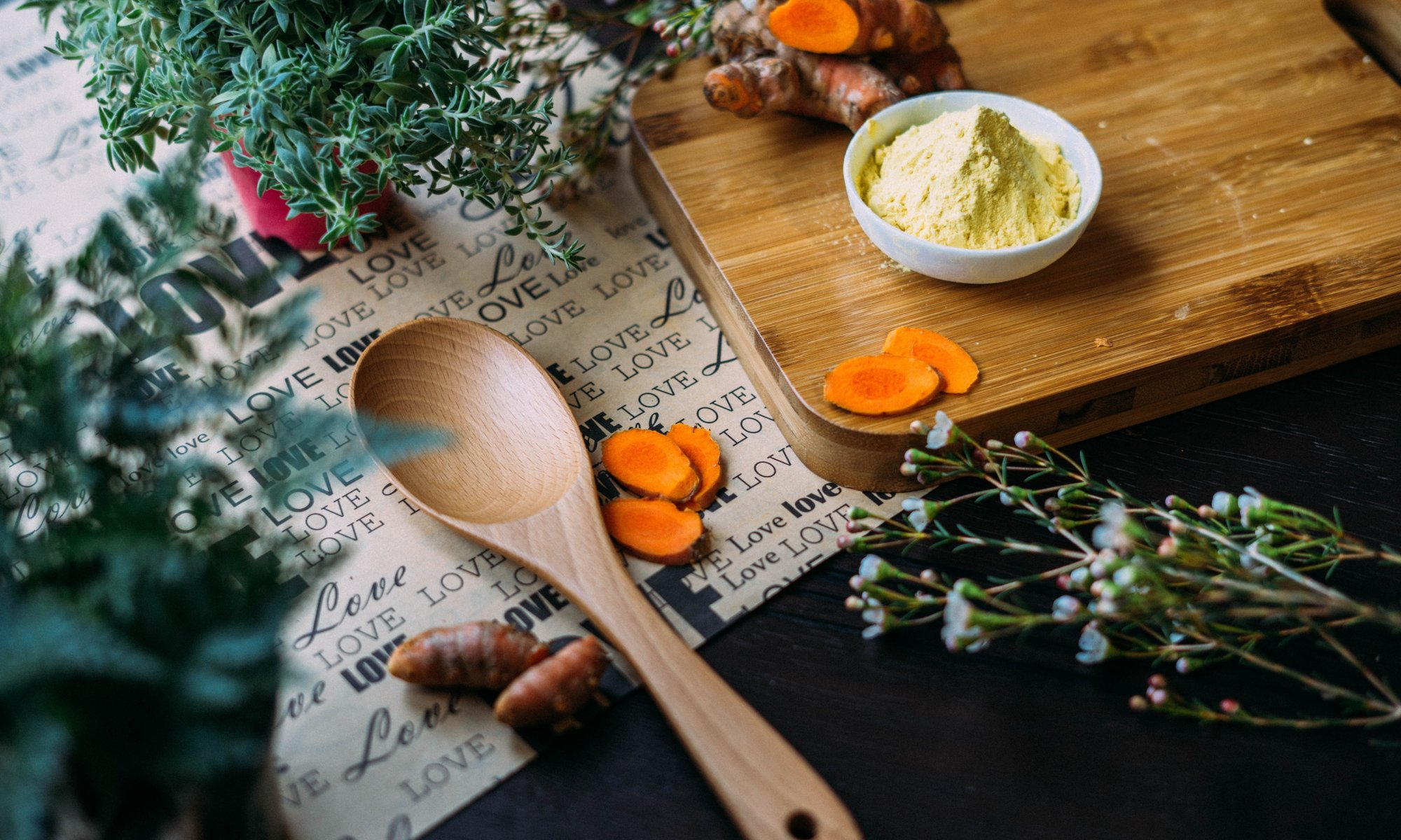 Chopping board with herbs, wooden spoon, and love background