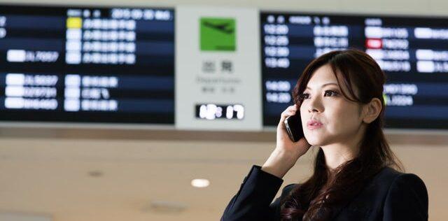 出発便表示の前に若い女性