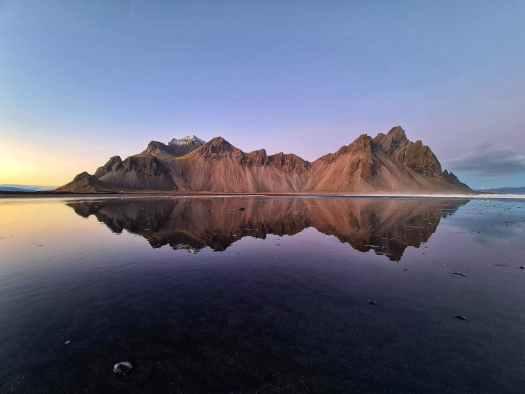 calm lake with glaciers near rocky island