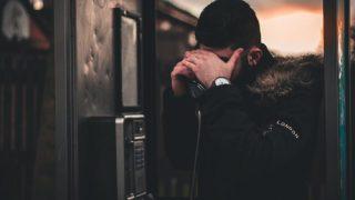 電話をかけながら悩む男性