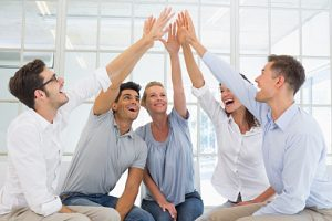 Group therapy in session sitting in a circle high fiving
