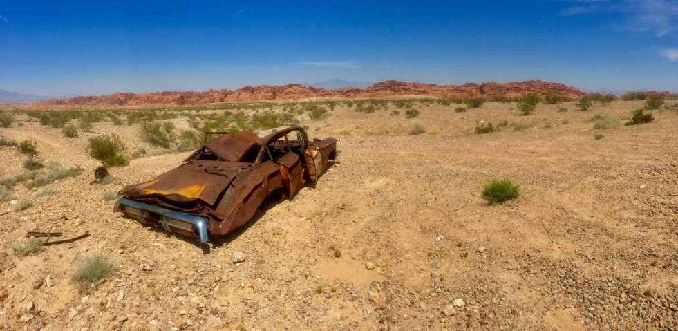 Rusted out burned and crushed car sits in the arid desert near Las Vegas
