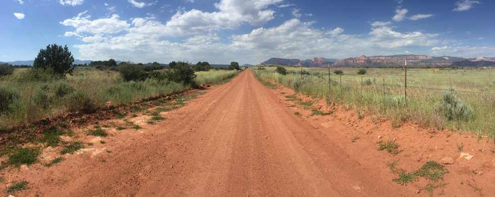 A red dirt road approaches Zion National Park