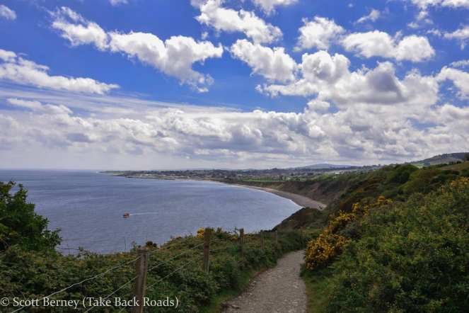 A blue sky shines over the Atlantic Ocean at the southern end of the cliff walk from Bray to Greystones in Ireland
