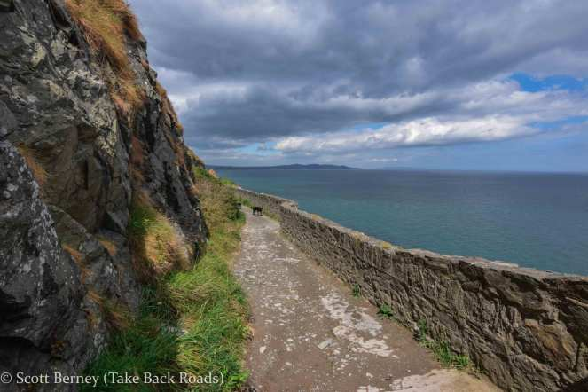 An old stone wall separates the cliff walk from the Atlantic Ocean on the hike from Bray to Greystones in Ireland