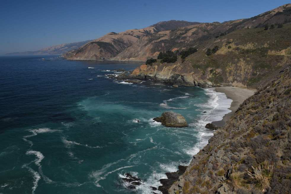 Bixby Bridge on the Pacific Coast Highway sits in the distance near the Pacific Coast Highway in Big Sur California