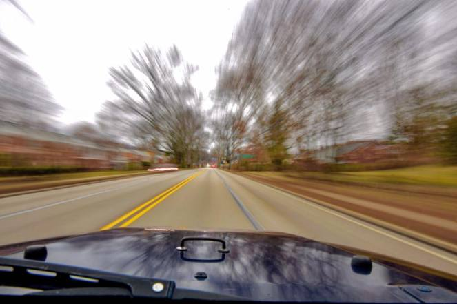 A back road blurs with motion above a blue jeep hood. Learn how to travel on back roads like this one.