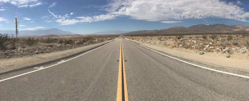 A back road stretches out under a broad blue sky in the middle of the California desert. Dusty mountains are visible in the distance. Learn how to travel on back roads like these.