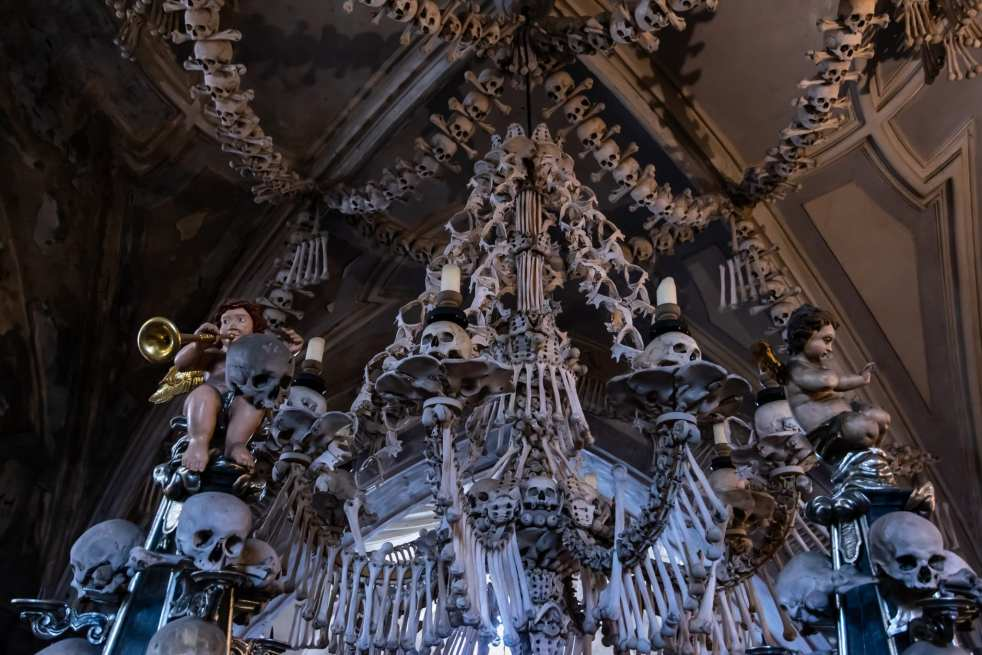 A bone chandelier made out of human bones and skulls adorned with cherubs and candles in the basement ossuary of the Sedlec bone church
