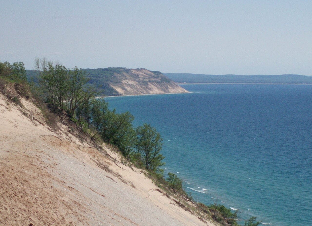 lake michigan coastline sleeping bear dunes blue water grey sky sandy scrubland