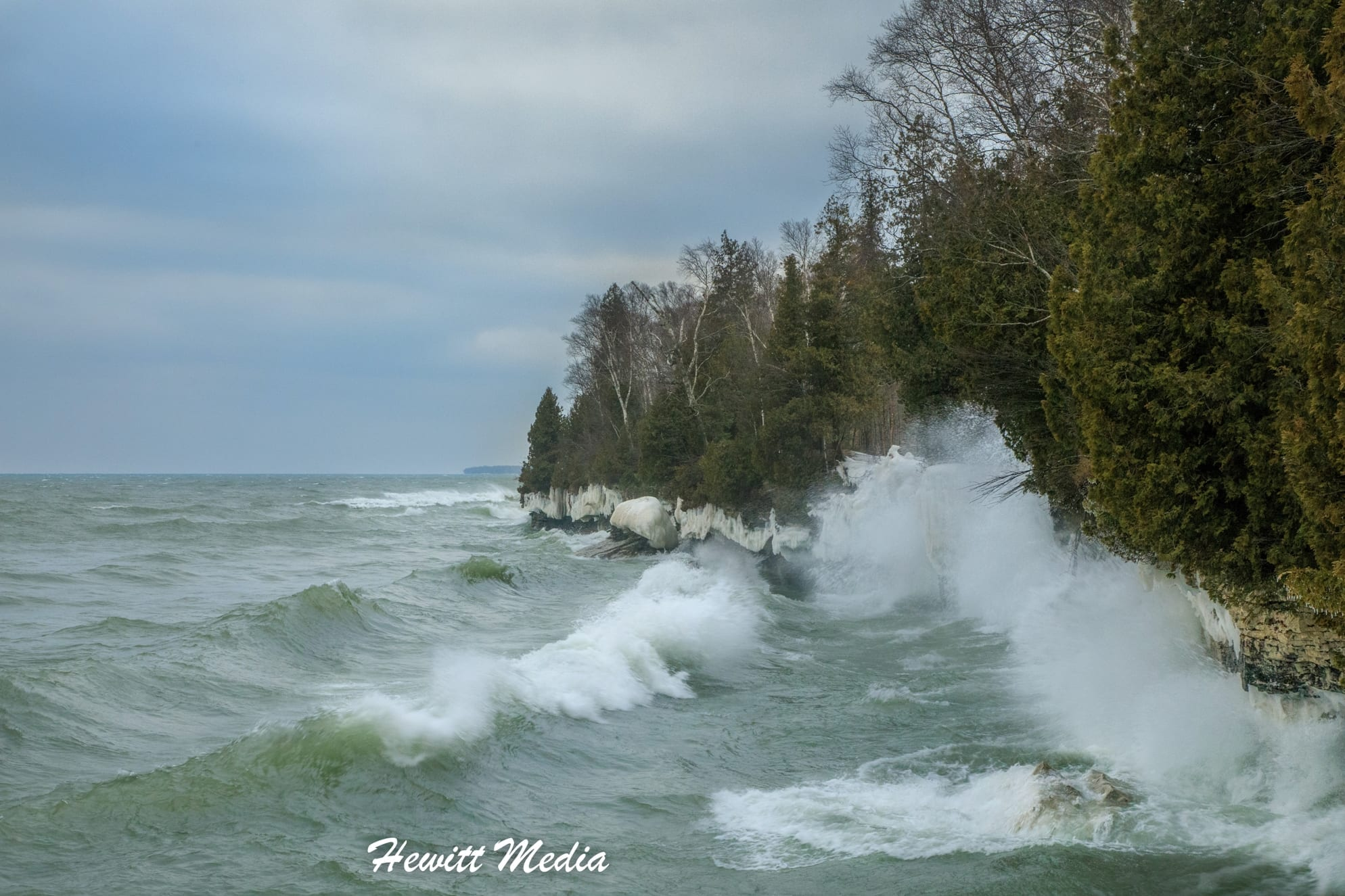 frigid waves crash along the shoreline forming ice and spray on the rocks and edge of the forest