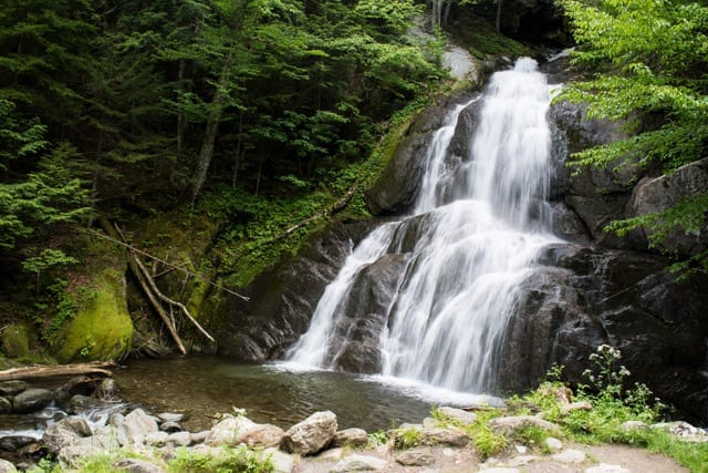 rushing waterfall flowing over rocks into a shallow creek surrounded by lush green forest moss glen falls granville VT