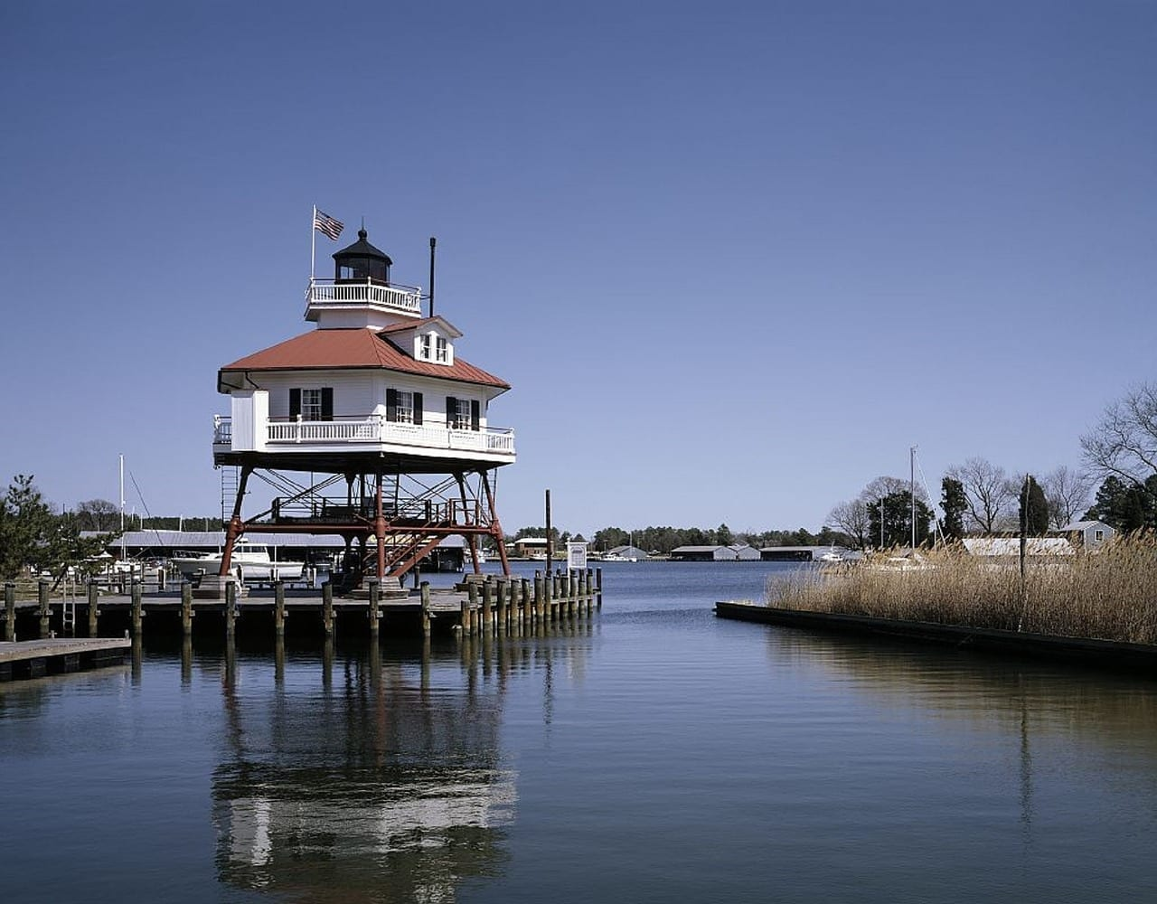 traditional chesapeake light house tower sits on the edge of the bay