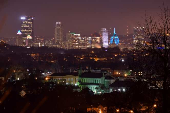 A large cathedral glows light green in the foreground, with the downtown Pittsburgh skyline off in the distance behind it.