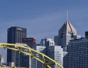 The UPMC and Highmark Buildings are pillars of the Pittsburgh Skyline, standing in front of a hazy blue sky, with the yellow Fort Duquesne bridge in the foreground and a hazy blue sky in the background.