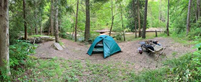 A green REI tent sits in a large opening in the woods, with a muddy brown creek in the background. This was on the final night of our cheap cross country road trip.