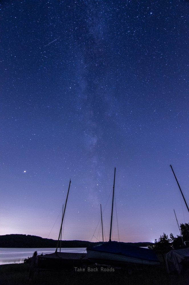Milky Way photography.  A shadowy marina and the masts of several boats frame the Milky Way and starry night sky overhead. A small glimpse of a nearby lake is visible. Starry sky.