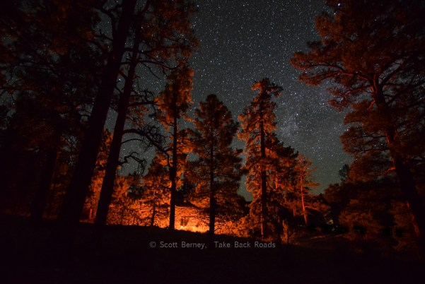 Night sky photography. camping photography. dark sky photo. A small wedge of the Milky Way, surrounded by other stars in a black night sky, peeks through the trees lit up by our campfire. Night sky photography equipment.
