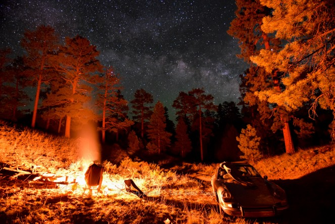 The Milky Way highlights the starry night sky over a campfire in the woods. The firelight outlines a camper sitting in front of it, creating a warm glow on the trees and an antique Porsche 911 nearby.
