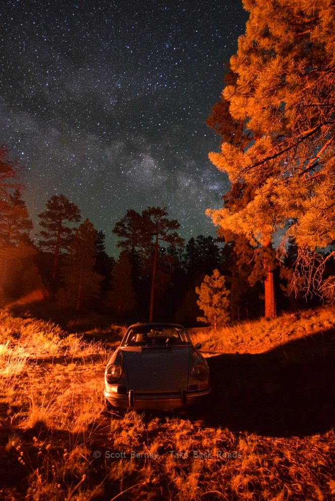 The orange and red light from a nearby campfire wash an antique Porsche 911 and the forest surrounding it with a warm glow and large shadows. The Milky Way streaks across the starry night sky overhead.