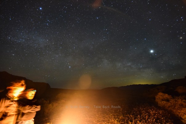 How to photograph the night sky. Two campers are bathed in warm light from their campfire, while the Milky Way stretches across a starry night sky. Learn what camera equipment you need to photograph the night sky.