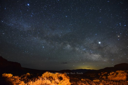 How to photograph the night sky. The Milky Way stretches diagonally across a blue black night sky above the Nevada desert. The foreground is lit up by a campfire.