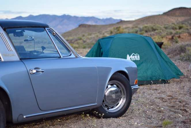 A grey Porsche 911 sits in front of a green REI tent in the Nevada desert. Sharp mountaintops split the horizon in the distance. What a cool wild campsite on our cheap cross country road trip.