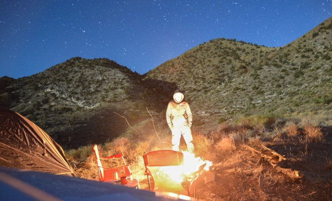 A faceless man stands in front of a bright campfire in the desert. He is surrounded by moonlit desert scrub with a blue starry night overhead. A tent and two camping chairs stand nearby.