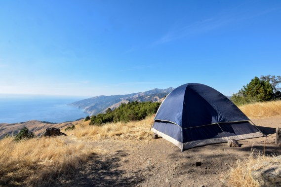 A large blue tent sits in a dispersed campsite on a hill in Big Sur, overlooking the Pacific Coast Highway and the cool blue waters of the Pacific Ocean. A brilliant blue sky overhead is nearly cloudless, and the wild grasses are dried and yellow. This campsite was free.