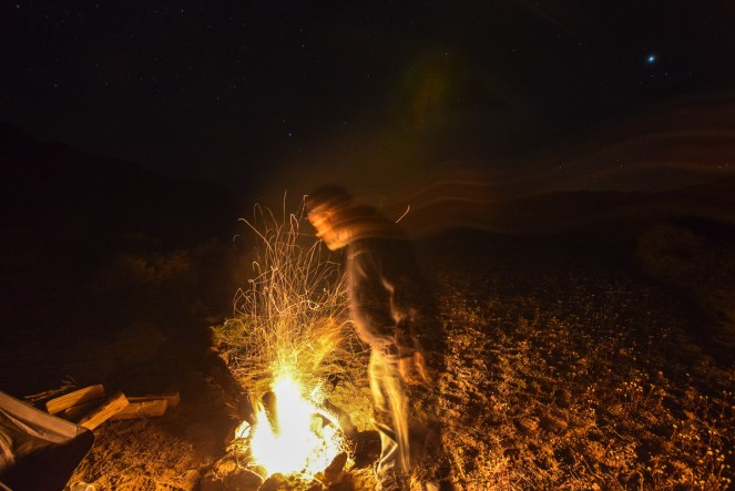 A man prods a small campfire in the desert, kicking numerous sparks up into the looming darkness