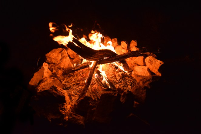 A peaceful campfire flickers within a natural stone fire ring.